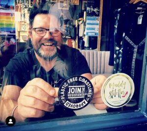 Mat McIvor proudly displaying our Plastic-Free sticker in the door of Fishboy PZ